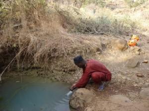 Prélèvement d'échantillon d'eau de source polluée par un enquêteur ARACFpt